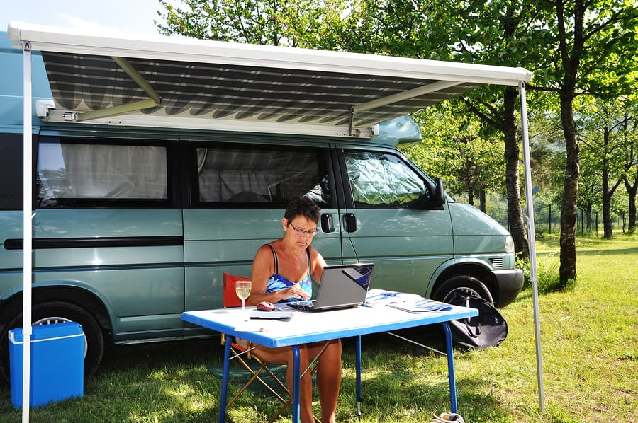 Lady Using Computer Next To Campervan